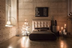 Modern empty bedroom in loft style with grey colors and wooden hand made Christmas tree with presents. warm and cozy. Modern empty bedroom in loft style with stock images