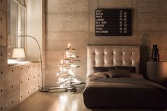 Modern empty bedroom in loft style with grey colors and wooden hand made Christmas tree with presents. warm and cozy. Modern empty bedroom in loft style with stock photography