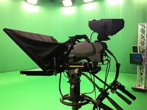 Modern empty green video. Recording and broadcasting studio with tv channel led screen and metalic stands, text prompter, lights on Stock Photos