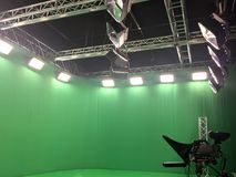 Modern empty green video. Recording and broadcasting studio with tv channel led screen and metalic stands, lights on Stock Photos
