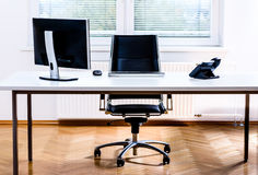 Modern empty office space desk with computer, phone and chair. Concept of corporate job vacancy, promotion, financial world and business in general Stock Images