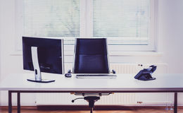 Modern empty office space desk with computer, phone and chair. Royalty Free Stock Images