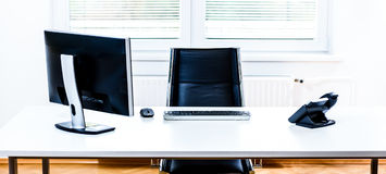 Modern empty office space desk with computer, phone and chair. Stock Photo