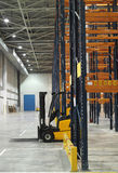 Modern empty storehouse. Modern white empty storehouse with loader and constructions Royalty Free Stock Photo