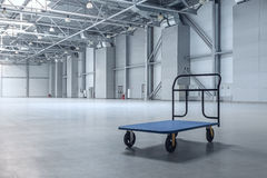 Modern empty storehouse. Interior of empty warehouse with a cart Stock Photos