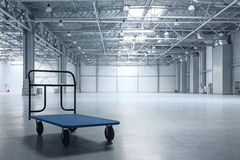 Modern empty storehouse. Interior of empty warehouse with a cart Royalty Free Stock Photo