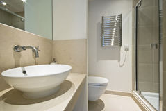 Modern en-suite bathroom. With round ceramic hand wash basin, toilet and shower Royalty Free Stock Images