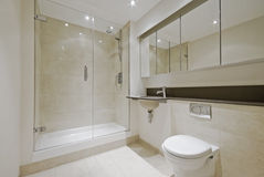 Modern en-suite bathroom. Luxury modern en-suite bathroom with floor to ceiling marble tiles Royalty Free Stock Photo