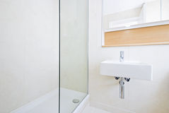 Modern en suite bathroom with large shower. White ceramic wash basin and natural stone tiled walls in beige Stock Photo