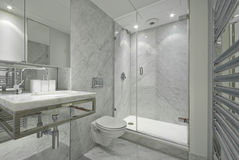 Modern en suite marble bathroom in white. Modern and contemporary en suite bahroom in marble white with designer fragments, shower, stylish wash basin and toilet Royalty Free Stock Image