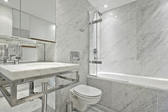 Modern en suite marble bathroom in white. Modern and contemporary en suite bahroom in marble white with designer fragments, large bath tub, stylish wash basin Royalty Free Stock Images