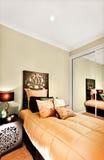 Modern enkel sovrumcloseup som fokuserar träsängen inklusive a Royaltyfri Foto