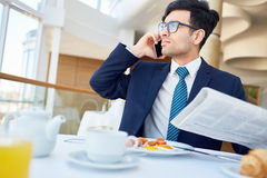 Modern entrepreneur. Busy entrepreneur with newspaper speaking on cellphone during breakfast or lunch Stock Image