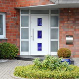 Modern entry door. With a front garden of the house - quadratsich Royalty Free Stock Photography