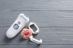 Modern epilator with accessories and flower. On wooden background Stock Images