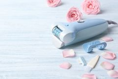 Modern epilator with accessories and flowers. On wooden background Royalty Free Stock Photos