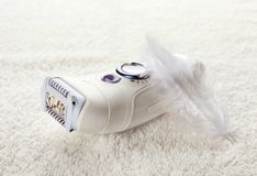 Modern epilator and feather. On soft towel Royalty Free Stock Photography