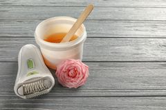 Modern epilator and plastic bucket with sugaring paste. On wooden background Royalty Free Stock Image