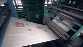 Modern equipment at a printing factory printing newspaper. 4K. stock footage