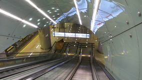 Modern escalator moving down, carrying passengers to underground subway station. Stock footage stock footage