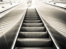 Modern escalator vertical transportation in the form of a moving staircase in black and white color. A Modern escalator vertical transportation in the form of a Royalty Free Stock Images