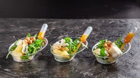 Modern European appetizer. Mini salad with gorgonzola, pear and roasted cashews. Orange dressing in sauceboat, capsule, pipette.