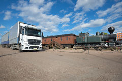 Modern European truck with trailer `Mercedes-Benz Actros` at an old train on a sunny June day. Kotka, Finland Royalty Free Stock Images
