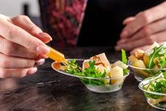 Modern Europees voorgerecht Minisalade met gorgonzola, peer en geroosterde cachou Sinaasappel die zich in juskom, capsule, pipet  stock foto