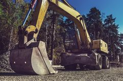 The modern excavator performs excavation work on the construction site royalty free stock photos