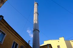 Modern exhaust pipe in an old residential area with low-rise buildings against a clean blue sky. Light gray color. Stairs. Against