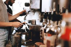 A modern expensive coffee machine is shown in work in modern cozy coffee shop. stock image