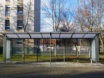 Modern exponeringsglas- och aluminiumbuskur i stads- inställning med den stenlade konkreta trottoaren arkivbild