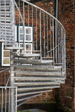 Modern exterior spiral staircase of metal in the backyard on an. Old brick building, fire escape in the old town Royalty Free Stock Photography