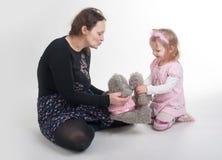 Modern förklarar till dottern en kyss på leksaker Royaltyfria Bilder