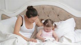 Modern försöker att lugna hennes dotter i sovrummet som ger hennes Smartphone Den gulliga lilla flickan med två hästsvansar är lager videofilmer