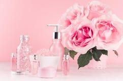 Modern f?rsiktig flickaktig badrumdekor - sk?nhetsmedel f?r badet, brunnsort, bukett av rosor, badtillbeh?r p? den mjuka vita tr? royaltyfria bilder