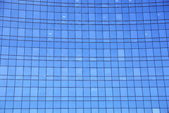 Modern facade of glass and steel reflecting sky and clouds. Stock Photo