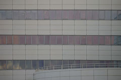 Modern facade with tinted windows. A modern facade with a series of tinted windows and a curved terrace Royalty Free Stock Images