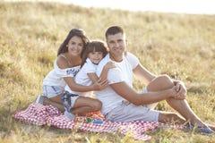 Modern, fadern och dottern vilar tillsammans inte i natur royaltyfri bild
