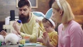 Modern, fadern och sonen målar ägg Den lyckliga familjen förbereder sig för påsk lyckliga easter Gullig pojke för litet barn lager videofilmer