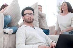 Modern familj i vardagsrummet i aftonen arkivbild