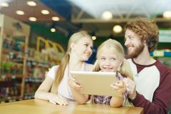 Modern family. Curious child with touchpad watching video with her parents near by stock photo