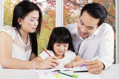 Modern family doing homework on table Royalty Free Stock Images