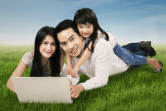Modern family with laptop on grass Stock Photo