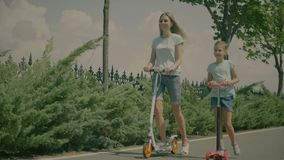 Modern family riding scateboard scooters in nature. Joyful elegant mother and smiling daughter riding scooters while family relaxing in summer park. Positive stock video