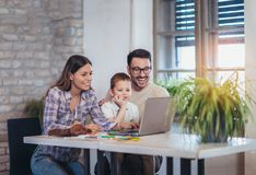 A modern family using a laptop. Mom, dad and their five year old son Royalty Free Stock Photos