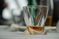 Modern fancy whiskey glass with golden alcoholic beverage on a white tablecloth surface as a symbol of drinking alcohol. Modern fancy whiskey glass with golden Stock Images