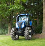 A modern farm tractor parked under trees in the summertime. A sturdy four wheel drive agricultural machine as seen at a pig farm in southern ontario Royalty Free Stock Photos