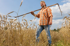 Modern farmer with scythe. At ripe wheat field Royalty Free Stock Photos