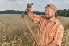 Modern farmer with scythe Stock Photography